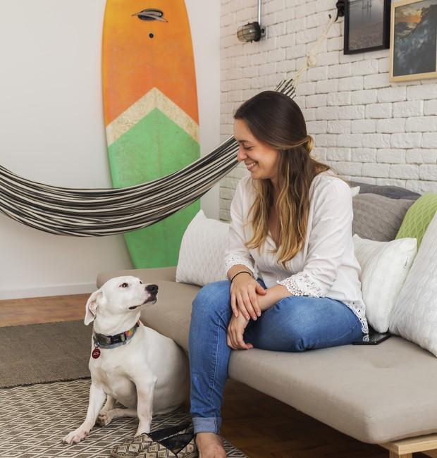 """A arquiteta Patrícia com sua cachorra Fuji, na sala de estar: """"Eu adoro chegar em casa e me jogar no sofá e abraçá-la!"""" (Foto: Rafael Renzo / Divulgação)"""