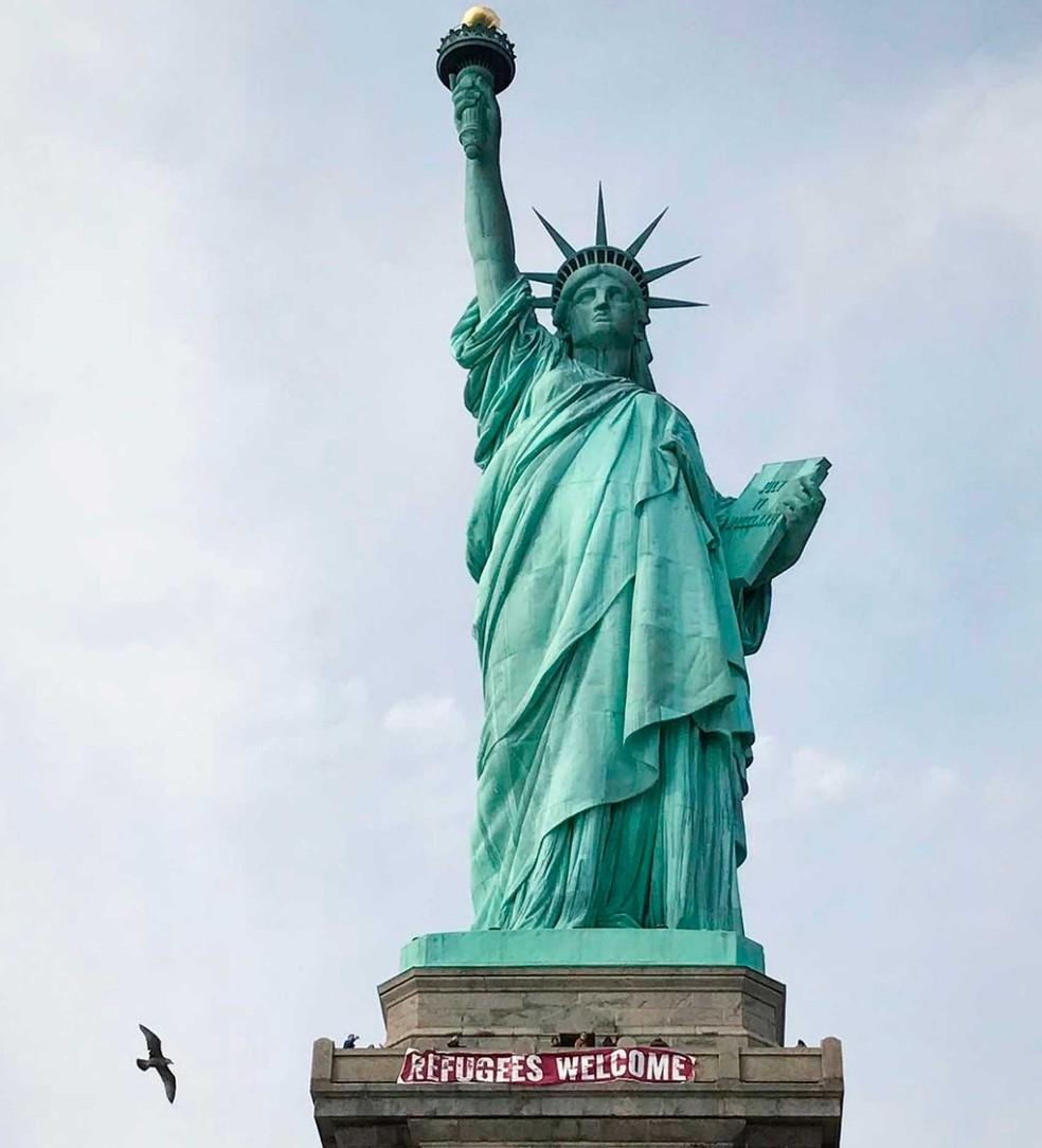 Faixa Colocada Na Estatua Da Liberdade Diz Que Refugiados Sao Bem Vindos on 77 Nova