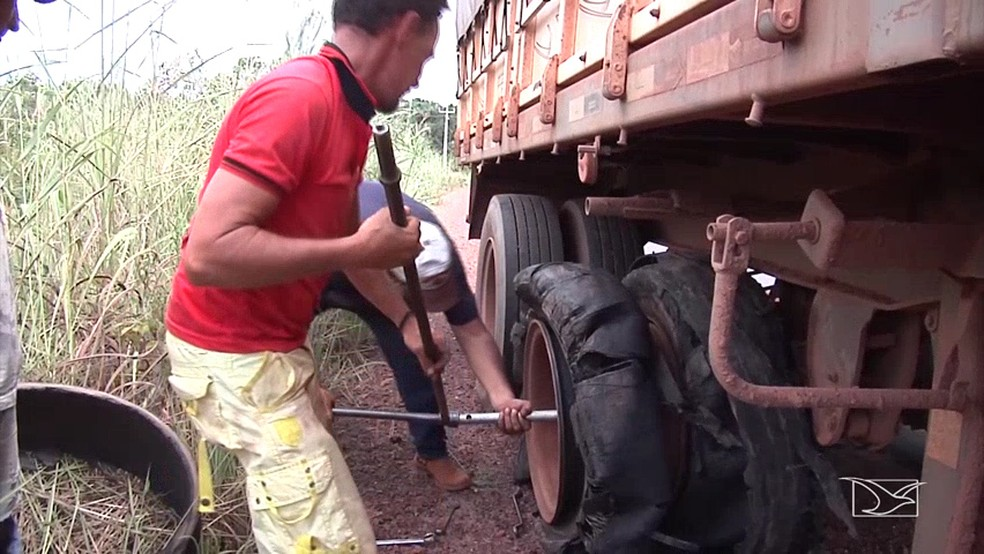Caminhoneiro Davi teve que descer no veículo para trocar pneu furado pelos buracos (Foto: Reprodução/TV Mirante)