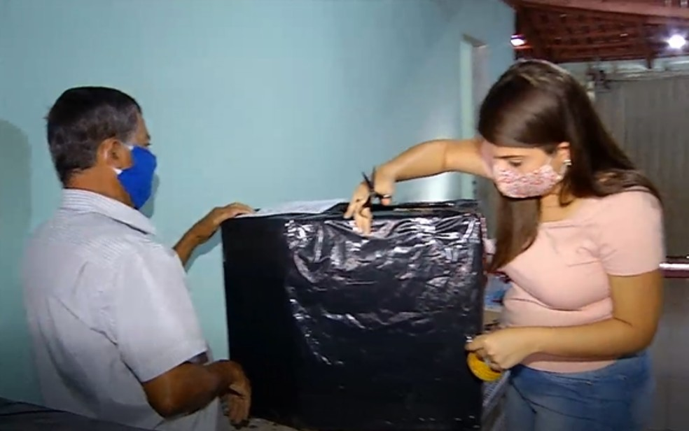 Avô ajuda a jovem durante a construção das casinhas, em Morrinhos — Foto: Reprodução/TV Anhanguera