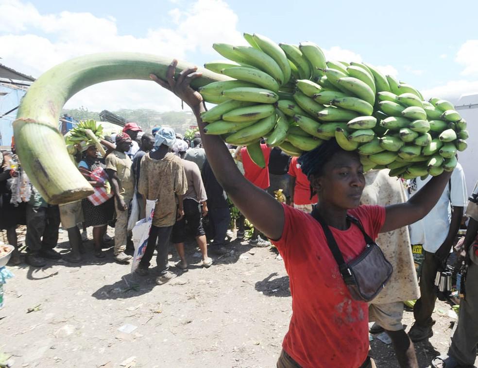 Mulher carrega bananas no mercado público em Cabaret, perto de Port-au-Prince. (Foto: Thony Belizaire/AFP)