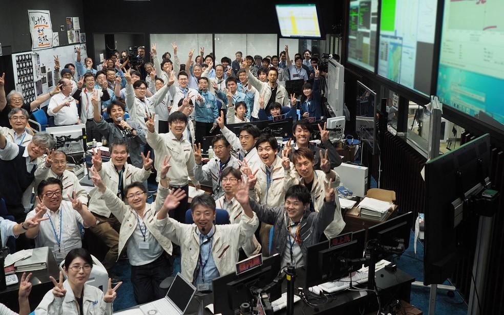 Imagem divulgada pelo Instituto de Ciências Espaciais e Astronáuticas (ISAS) da Agência de Exploração Aeroespacial do Japão (JAXA) mostra pesquisadores e funcionários comemorando após receberem a confirmação da aterrissagem da Hayabusa2 no asteroide Ryugu — Foto: Yutaka Iijima / ISAS-JAXA / via AFP Photo
