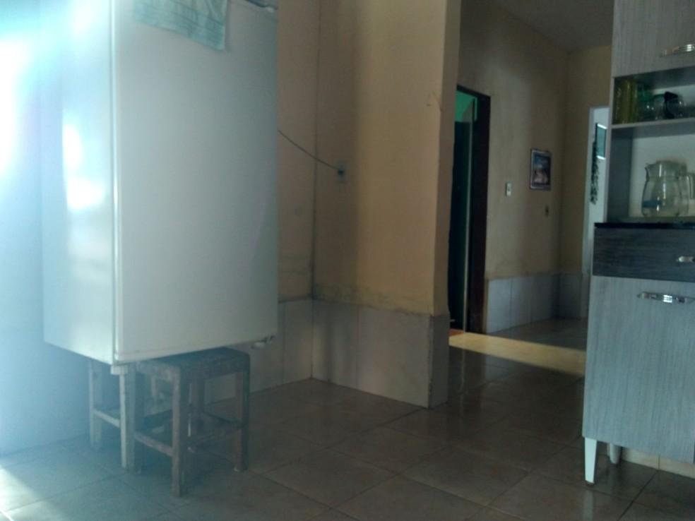 Moradora colocou geladeira sobre cadeiras para proteger da água (Foto: Carlos Rocha / G1)