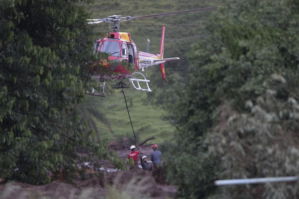 Bombeiros se preparam para suspender, com um helicóptero, um corpo resgatado da lama depois do rompimento da barragem da Vale, em Brumadinho. — Foto: Leo Correa/AP