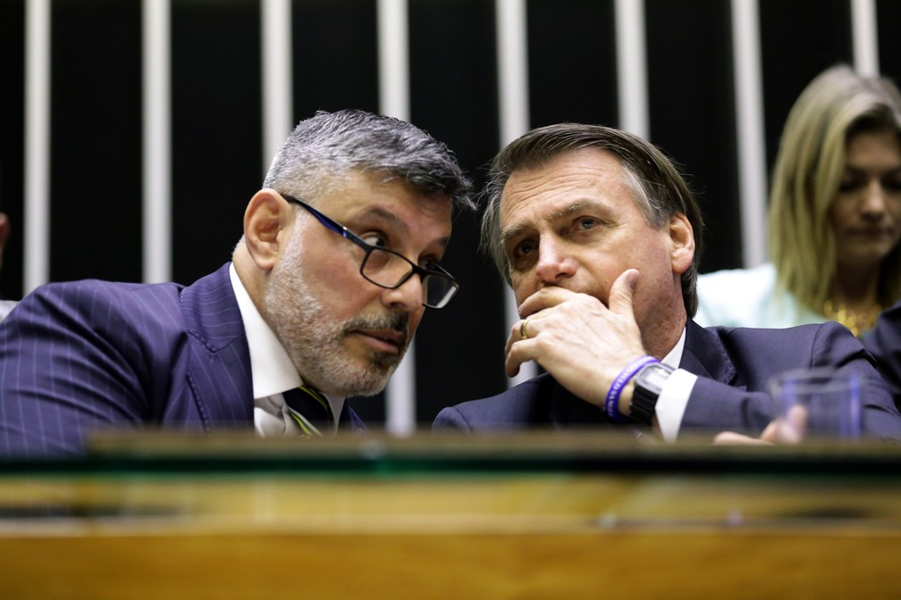O presidente Jair Bolsonaro conversa com o deputado Alexandre Frota no plenário da Câmara durante solenidade em maio deste ano  Foto: Michel Jesus/ Câmara dos Deputados
