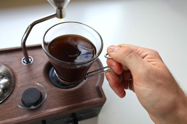 Após aquecer, água passa pelo coador do despertador cafeteira e entrega uma xícara de café pronta (Foto: Divulgação)