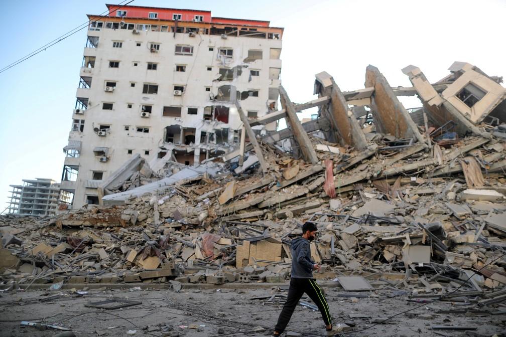 Um menino palestino passa pelos restos de uma torre que foi destruída em ataques aéreos israelenses na cidade de Gaza na quarta (12)  — Foto: Suhaib Salem/Reuters