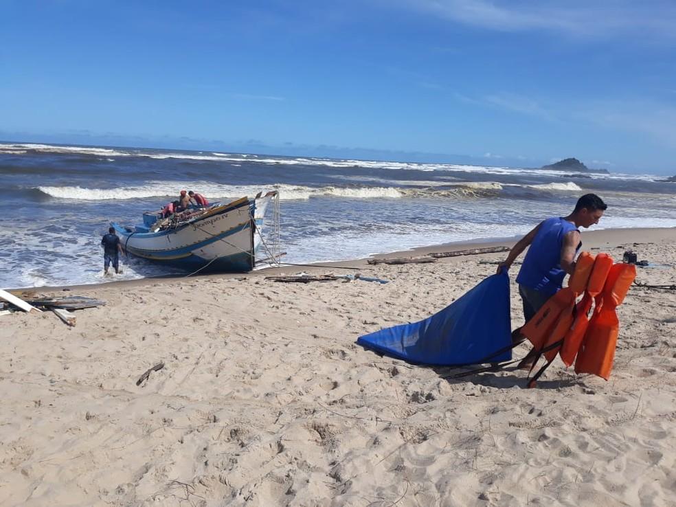 Pescadores retiram coletes do barco Pampo IV, que virou no mar em Itanhaém (SP) — Foto: João Amaro/G1