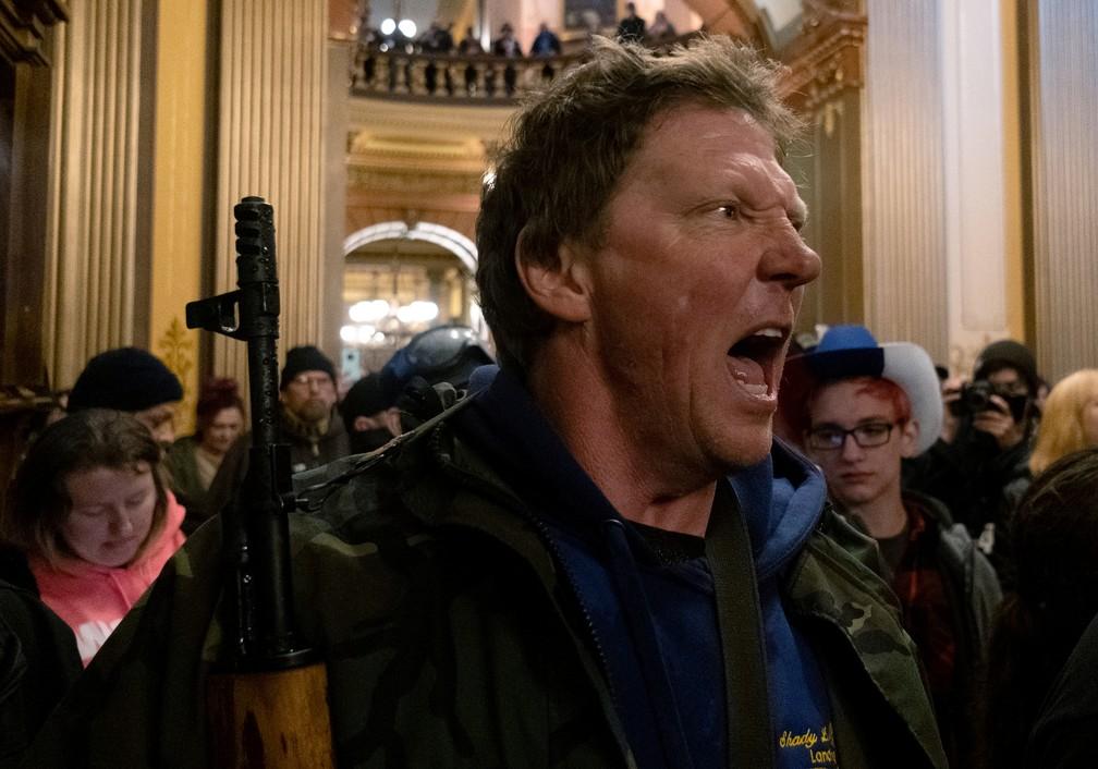 Armado, manifestante ocupa o Congresso do Michigan para protestar contra isolamento social nesta quinta-feira (30) — Foto: Seth Herald/Reuters