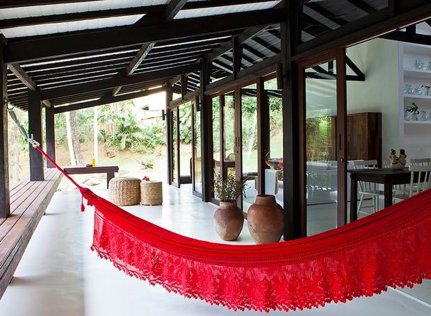 A varanda, projetada pelo designer de interiores Gabriel Valdivieso para o seu irmão, Cícero, tem uma rede vermelha. A casa com jeito de cabana fica em Penedo, ao sul do Rio de Janeiro (Foto: Lufe Gomes/Casa e Jardim)