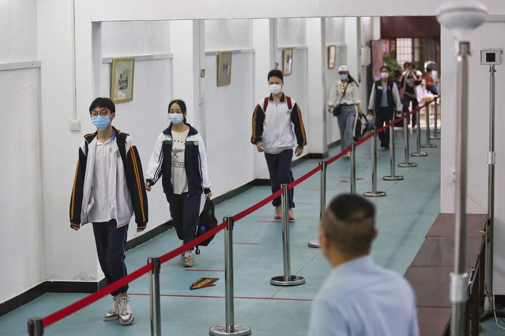 Estudantes em Wuhan mantêm distância e usam máscaras ao chegar à escola em imagem de arquivo — Foto: Chinatopix/AP/Arquivo