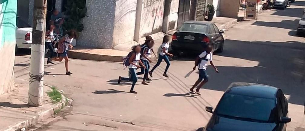 Crianças correm por ruas da Maré durante tiroteio e sobrevoo de helicóptero da polícia na comunidade — Foto: Reprodução / Maré Viva