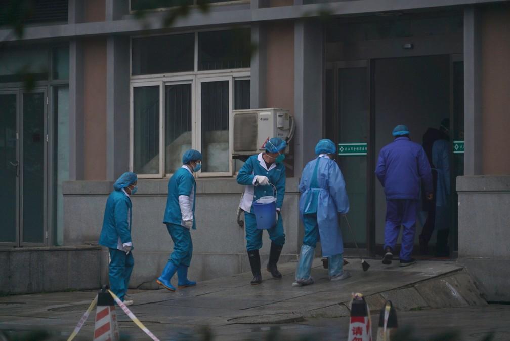 Funcionários do hospital lavam a entrada de emergência do Centro de Tratamento Médico de Wuhan, na China, onde alguns infectados com um novo vírus estão sendo tratados — Foto: AP Photo/Dake Kang
