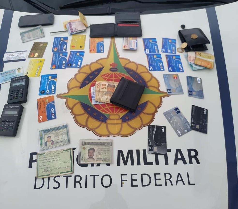 Durante a abordagem foram encontrados mais de 20 cartões de crédito, maquinas de cartões, dinheiro e dispositivos que eram instalados nos caixas eletrônicos. — Foto: PMDF/ Divulgação