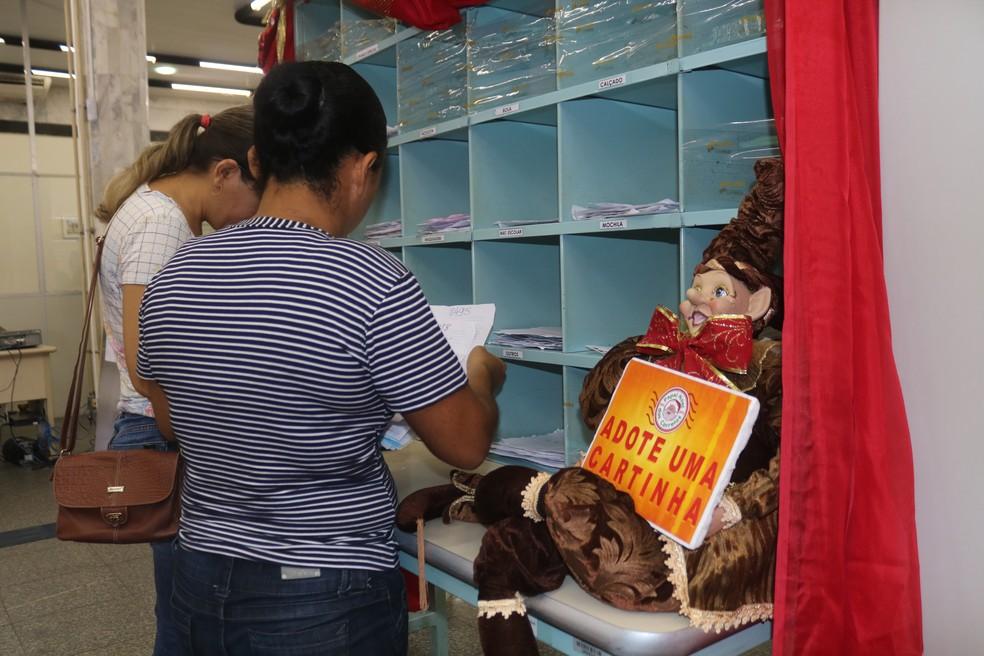 Mulheres escolhem cartinhas na agência dos Correios — Foto: Gilcilene Araújo/G1