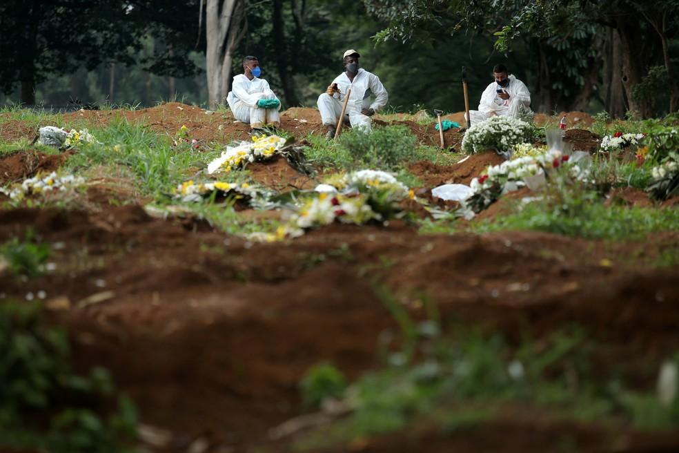 Coveiros com trajes de proteção aguardam para enterrar vítima da Covid-19 no Cemitério da Vila Formosa, na Zona Leste de São Paulo, nesta terça-feira (9) — Foto: Carla Carniel/Reuters