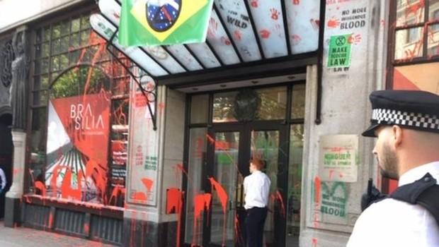 Manifestantes picharam a fachada da embaixada brasileira com tinta vermelha, simbolizando o 'sangue derramado', dos indígenas; rapaz está 'colado' à porta (Foto: FERNADA ODILLA/BBC)