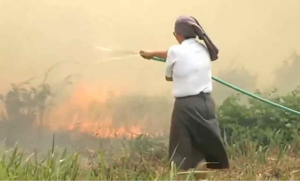 Monja usa balde e mangueira para proteger templo religioso de incêndio em Fortaleza — Foto: Paulo Sadat/SVM