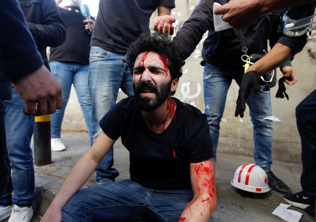 Manifestantes ajudam homem ferido após confronto com exército libanês durante protesto contra as crescentes dificuldades econômicas e para marcar o Dia do Trabalho, em Beirute, no Líbano — Foto: Mohamed Azakir/Reuters