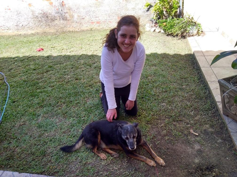 Franciny Tortato Silva, de 19 anos, que espera pelo transplante de pulmão, brinca com o cachorro 'Black' no quintal de casa. (Foto: Arquivo pessoal)