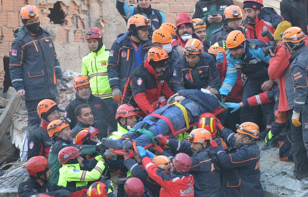 Equipes de resgate carregam sobrevivente de desabamento de prédio residencial após terremoto em Elazig, na Turquia — Foto: Stringer/Reuters