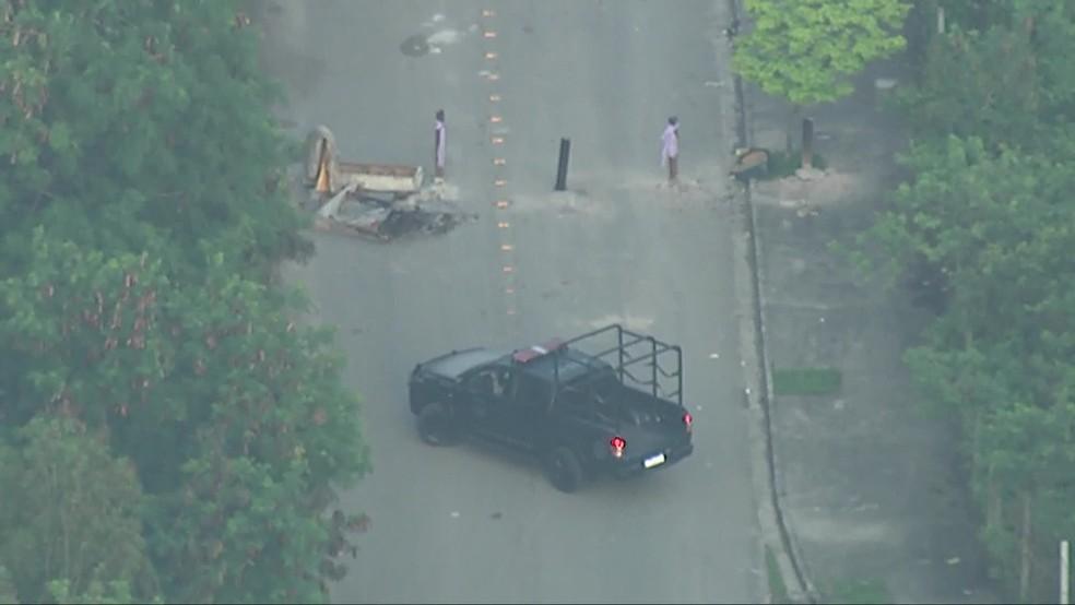 Carro da polícia não consegue passar em barricada na Cidade de Deus, na Zona Oeste do Rio — Foto: Reprodução/ TV Globo