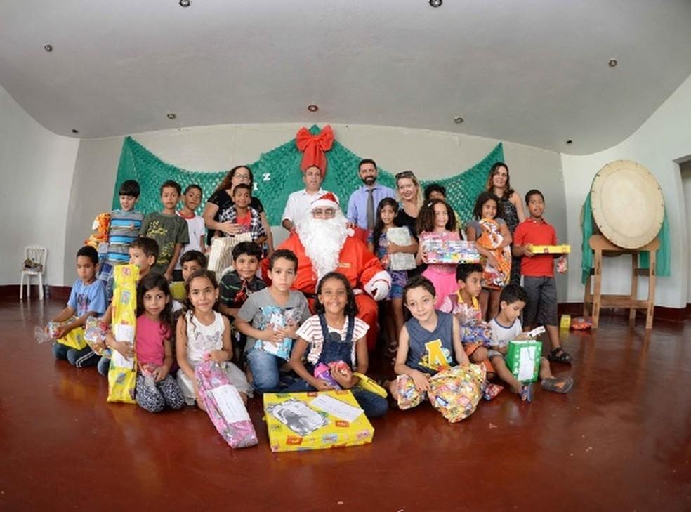 Papai Noel entrega presentes de Natal para crianças.  (Foto: Correios/Divulgação )