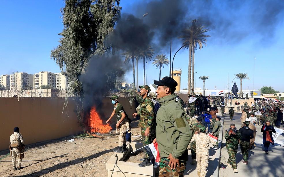 Combatentes de forças paramilitares atearam fogo ao muro da embaixada dos Estados Unidos, em Bagdá, no Iraque, durante protesto desta terça-feira (31)  — Foto: Thaier al-Sudani/ Reuters