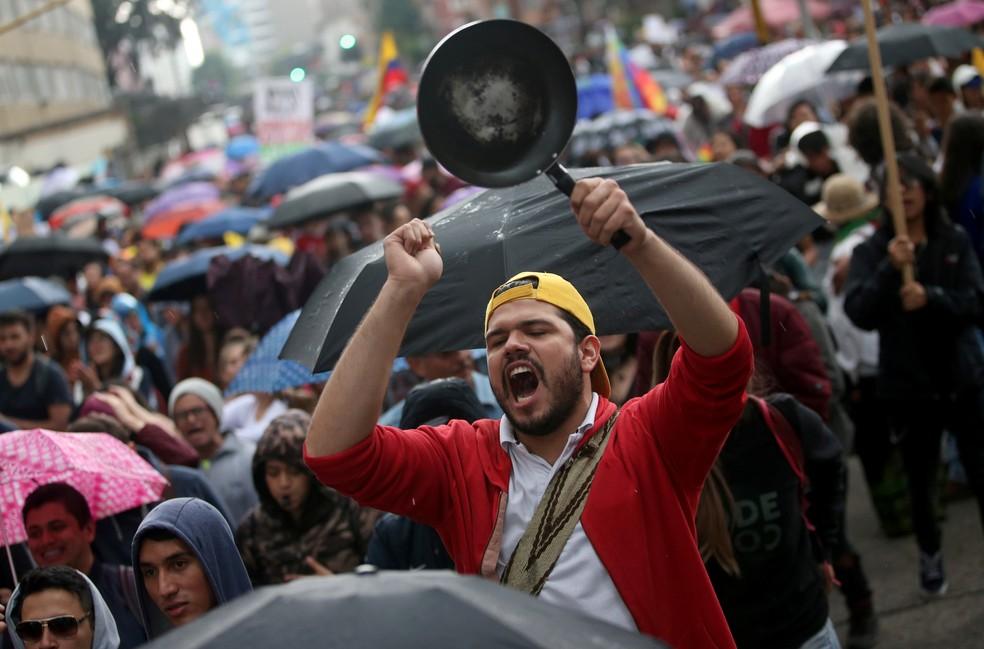 Um homem bate panela durante protesto combinado com shows musicais em Bogotá, na Colômbia, neste domingo (8) — Foto: Luisa Gonzalez/Reuters