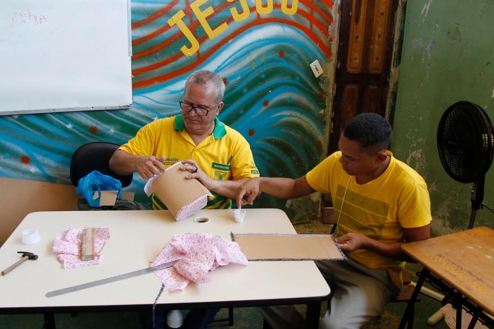 O instrutor Luiz Leite (e) ensina os detalhes da técnica de confecção de bolsas (Foto: Akira Onuma / Divulgação / Susipe)
