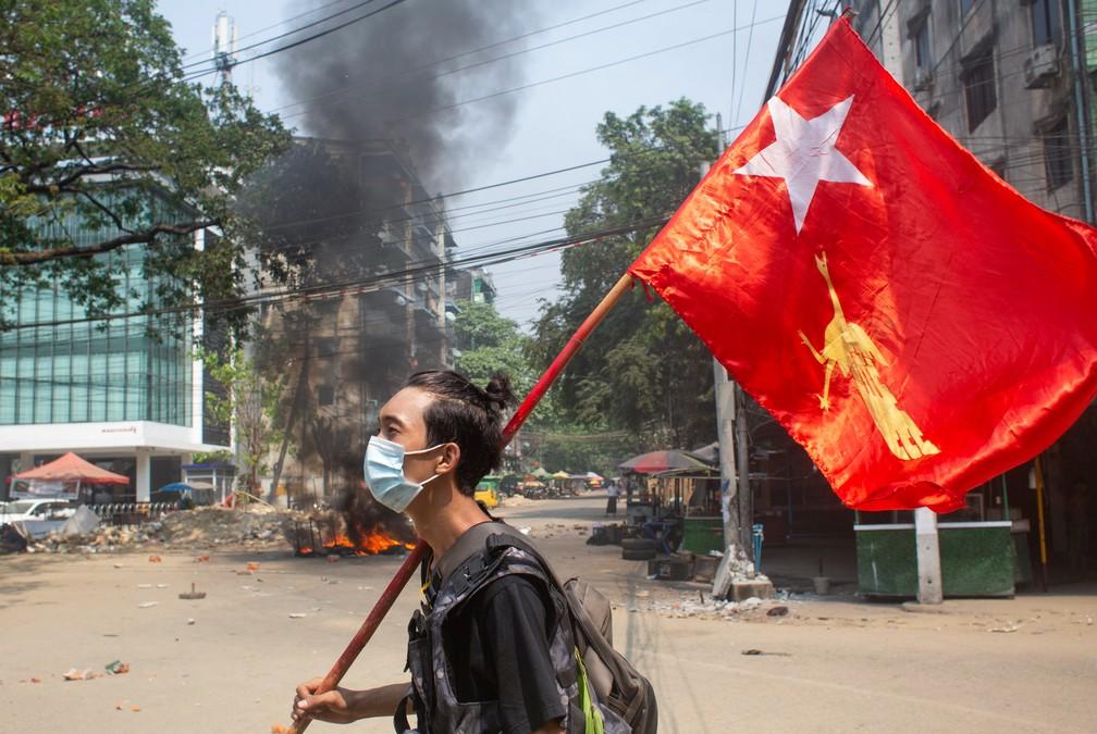 Homem segura bandeira da Liga Nacional para a Democracia durante protesto em Mianmar  — Foto: Reuters