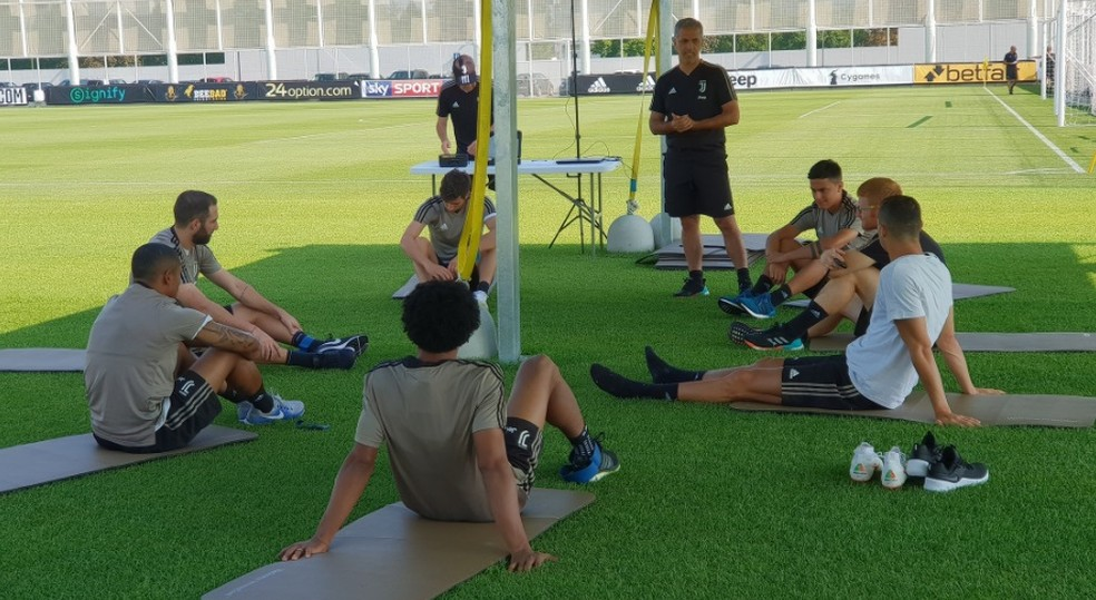 De camisa branca, Cristiano Ronaldo descansa entre exercícios no CT da Juventus, em Turim (Foto: Reprodução de Twitter)