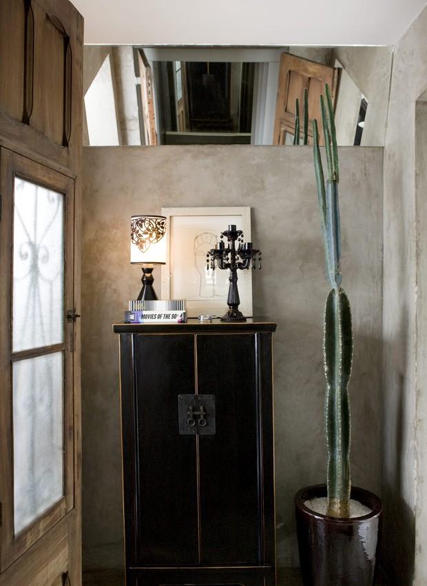 Hall de entrada da arquiteta Leticia Nobell, com armário, vaso de planta, castiçal preto, abajur, e espelho inclinado, ao fundo parede cinza. No hall de entrada da arquiteta Leticia Nobell, o espelho inclinado dá profundidade ao ambiente. (Foto: Edu Castello)