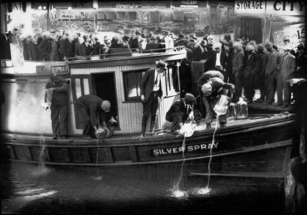 Em foto de 1922, pessoas observam agentes da proibição despejarem rum de garrafões de cinco litros no Rio Elizabeth, em Norfolk, Virginia — Foto: Charles S. Borjes/The Virginian-Pilot via AP
