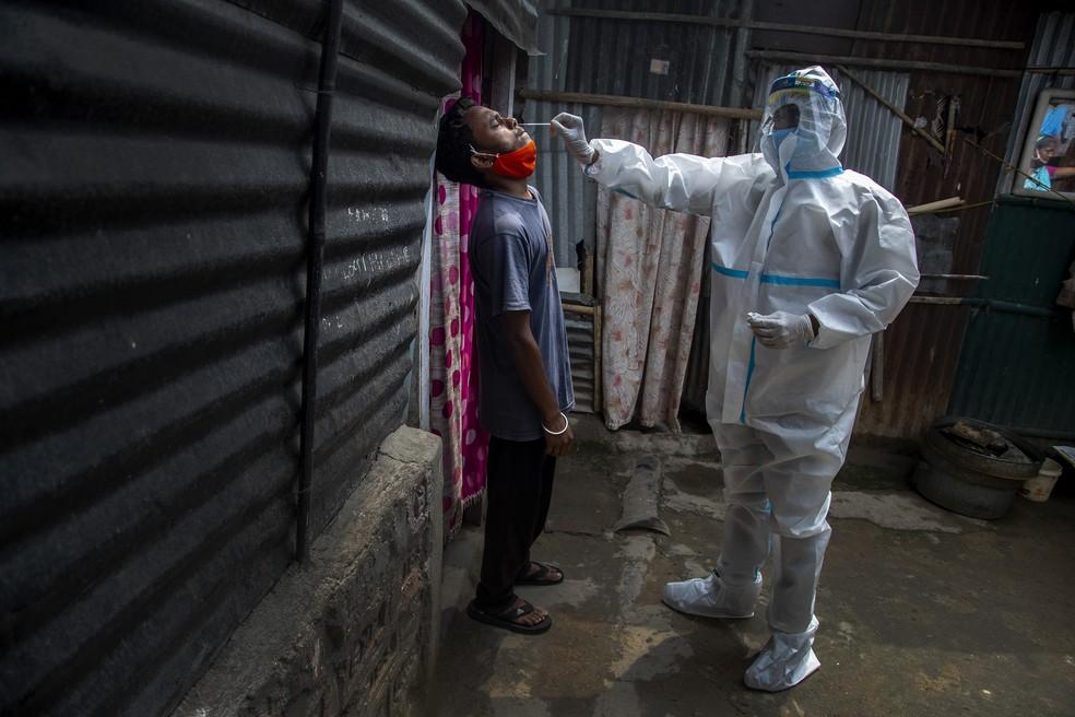 Trabalhador da saúde, vestindo traje de proteção, usa swab nasal para realizar teste de Covid-19 em um bairro pobre de Gauhati, no estado de Assam, na Índia, em 17 de maio de 2021 — Foto: Anupam Nath/AP
