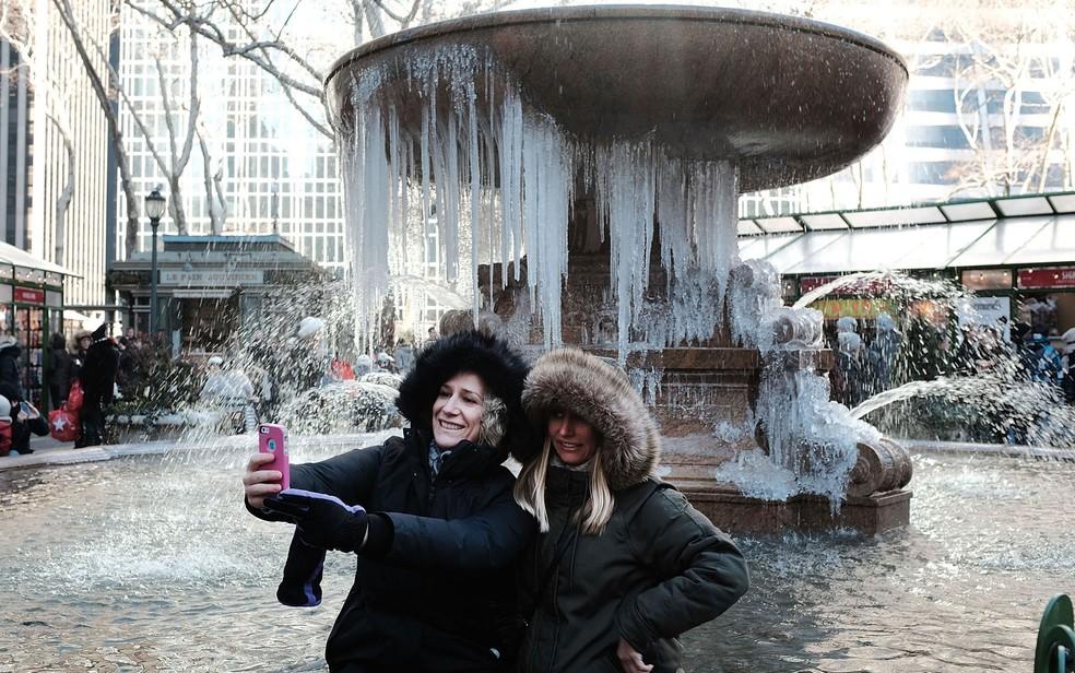 Turistas em Nova York aproveitaram para tirar fotos em frente a uma fonte congelada no Bryant Park (Foto: Spencer Platt/Getty Images North America/AFP)