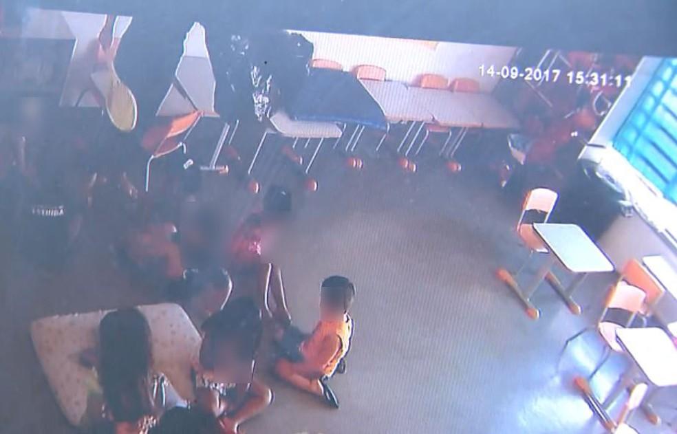 Na parte superior da foto, a estagiária segura a raquete e o saco de lixo para intimidar as crianças em Restinga, SP (Foto: Câmeras de segurança)