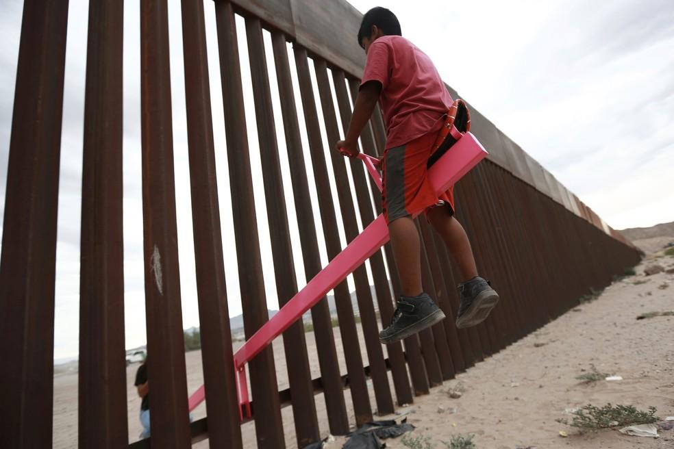 Uma criança brinca em uma gangorra instalada na cerca que divide a fronteira entre o México e os EUA em Ciudad de Juarez — Foto: Christian Chavez/Reuters