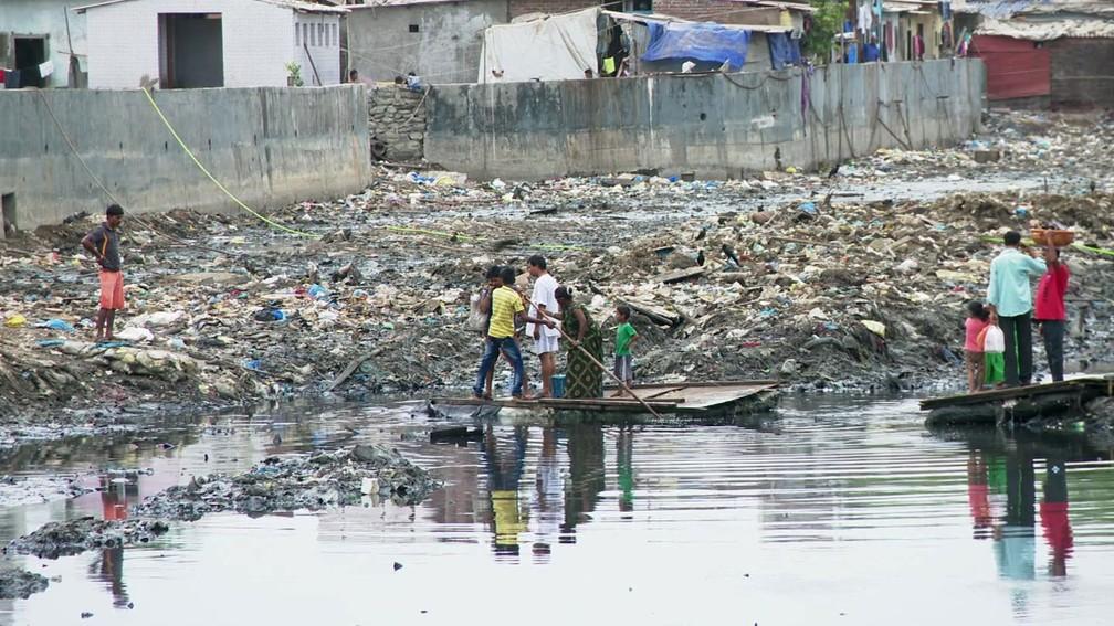 Balsa improvisada feita de isopor é transporte barato para para moradores de uma favela na Índia (Foto: Reprodução/BBC)