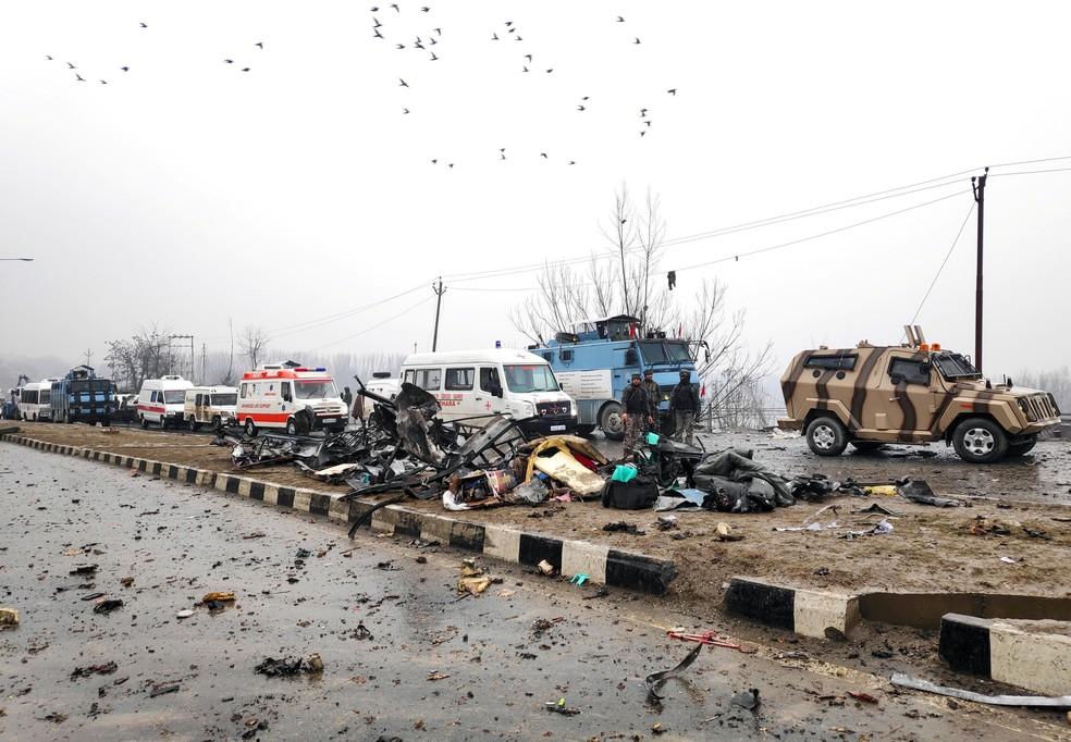 Soldado indiano examina destroços de veículos atingidos por explosão de carro-bomba na quinta-feira (14) na Caxemira — Foto: Younis Khaliq/Reuters