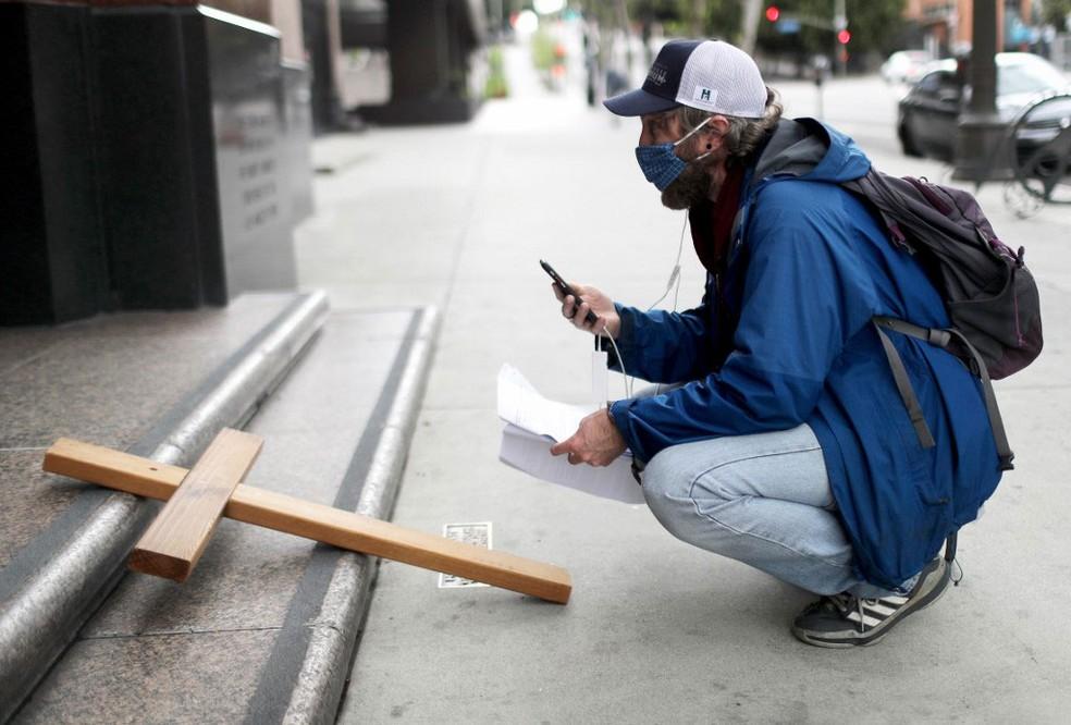 Ativista católico transmite pelo smartphone via crucis em Los Angeles, na Califórnia, na sexta-feira (10) — Foto:  Mario Tama / Getty Images via AFP