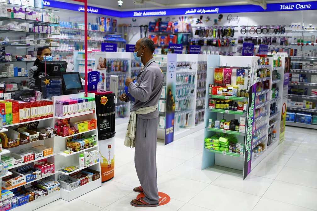 6 de abril - Um trabalhador usa máscara de proteção ao comprar remédios em uma farmácia, em Dubai, Emirados Árabes Unidos — Foto: Ahmed Jadallah/Reuters