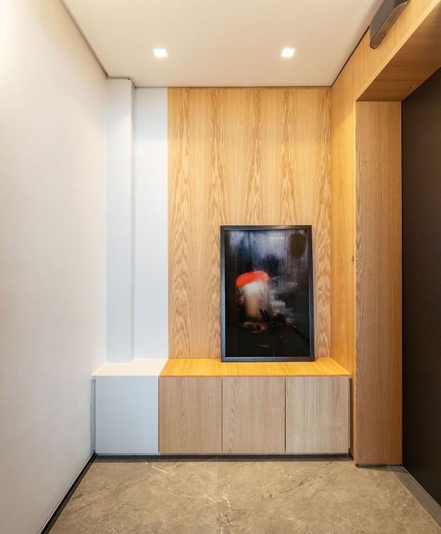 HALL DE ENTRADA | A mesma madeira usada no painel que encapa o living segue para o hall de entrada (Foto: Maura Mello/ Divulgação)