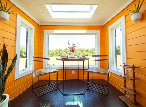 Aos fundos, uma pequena área para refeições possui paredes laranja (Foto: Cindy Ord/ Reprodução)