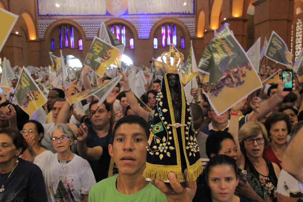 Fiel adolescente segura imagem de Nossa Senhora Aparecida na principal missa do dia 12 de outubro de 2019 — Foto: Carlos Santos/ G1
