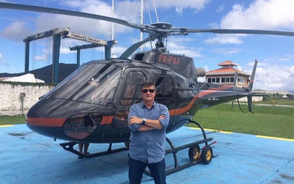 Coronel Edson Luiz Gaspar posa ao lado de helicóptero de Felipe Ramos; aeronave foi apreendida (Foto: Redes sociais)