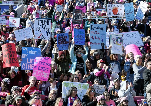 """LAS VEGAS, NV - JANUARY 21:  (EDITORS NOTE: Image contains profanity) Attendees hold signs during the Women's March """"Power to the Polls"""" voter registration tour launch at Sam Boyd Stadium on January 21, 2018 in Las Vegas, Nevada. Demonstrators across the  (Foto: Getty Images)"""