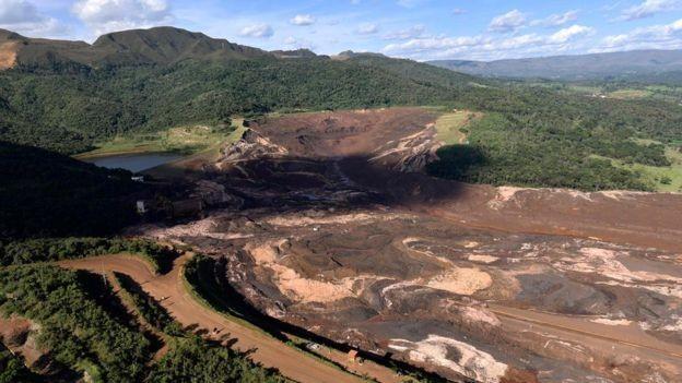 """Visão da barragem da mina Córrego de Feijão após o rompimento; a estrada onde estava o caminhão de Ana Paula fica à direita do entroncamento em """"v"""", tomada parcialmente pela lama (Foto: AFP via BBC News Brasil)"""