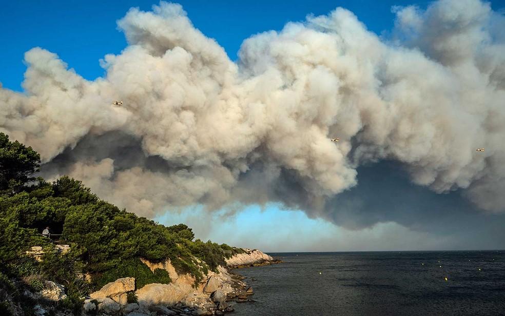 Três aviões dos bombeiros enfrentam coluna de fumaça provocada por incêndio florestal no Sul da França — Foto: Xavier Leoty / AFP Photo