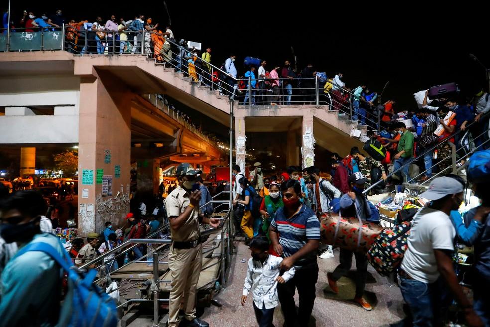 Trabalhadores chegam a estação de ônibus em Ghaziabad, nos arredores de Nova Délhi, para retornar às suas aldeias na segunda (19) após o governo ordenar um lockdown de 6 dias para tentar frear a 2ª onda de Covid-19 na Índia — Foto: Adnan Abidi/Reuters